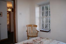 another bedroom view showing a chair, window and hallway at half moon house in reeth